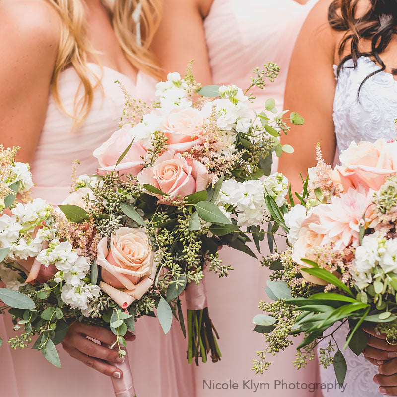 Bride's maids showing off their pastel colored bouquets.