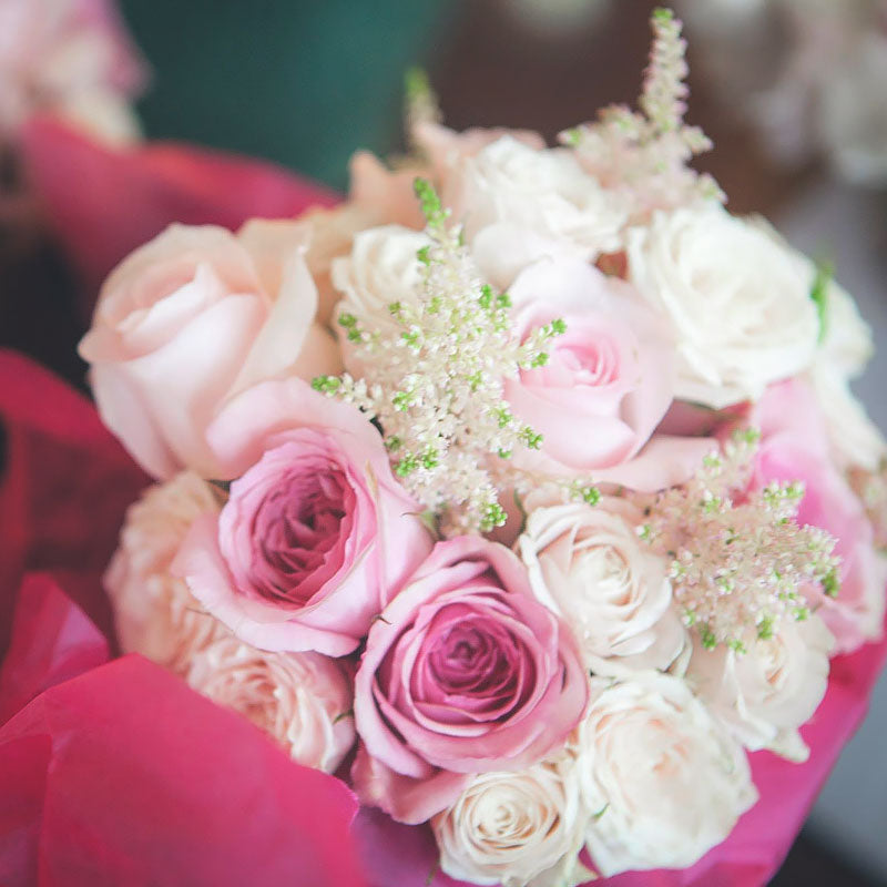 Close up photo of wedding bouquet with a mix of pink and white flowers including Roses.