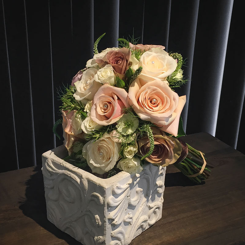 Bridal bouquet with a mix of pastel colored Roses and simple greenery accents.