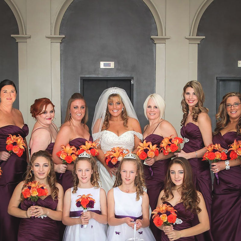 A bride and her large bridal party posing with their bouquets during her Autumn wedding.