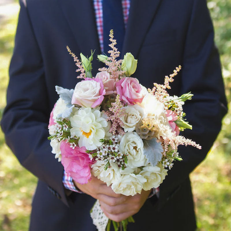 Groom holding his bride's bouquet which feature a mix of Roses in soft pink and white colors.