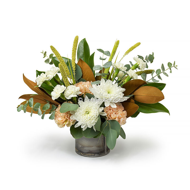 Fall flower arrangement with white mums, white mini carnations, soft peach carnations, millet, Eucalyptus and Magnolia leaves arranged in a rustic tin cylinder.