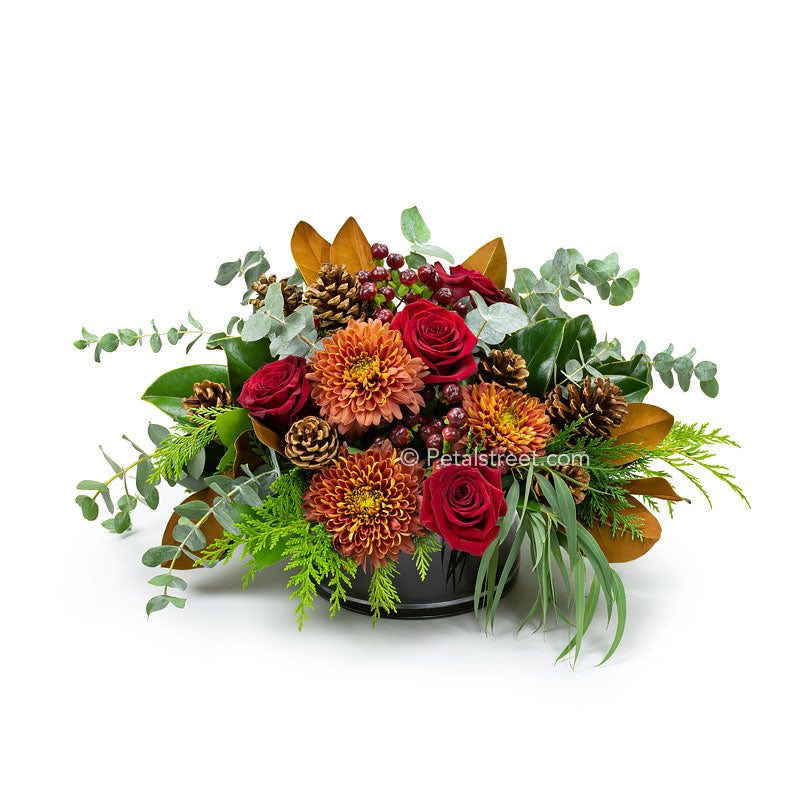 Red Roses, rust colored Mums, Eucalyptus, red Berries, Pine Cones, and Magnolia Leaves arranged in a low cylinder vase, an ideal table centerpiece.