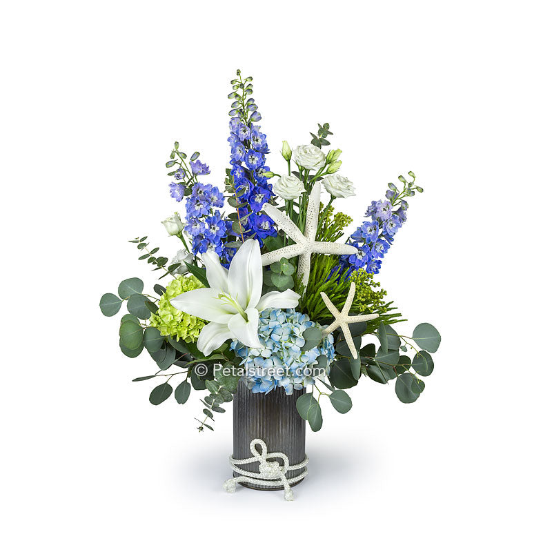 Beach flowers or nautical flowers with Lilies, Hydrangea, Delphinium, Eucalyptus, and Starfish in a tin container with rope accent.