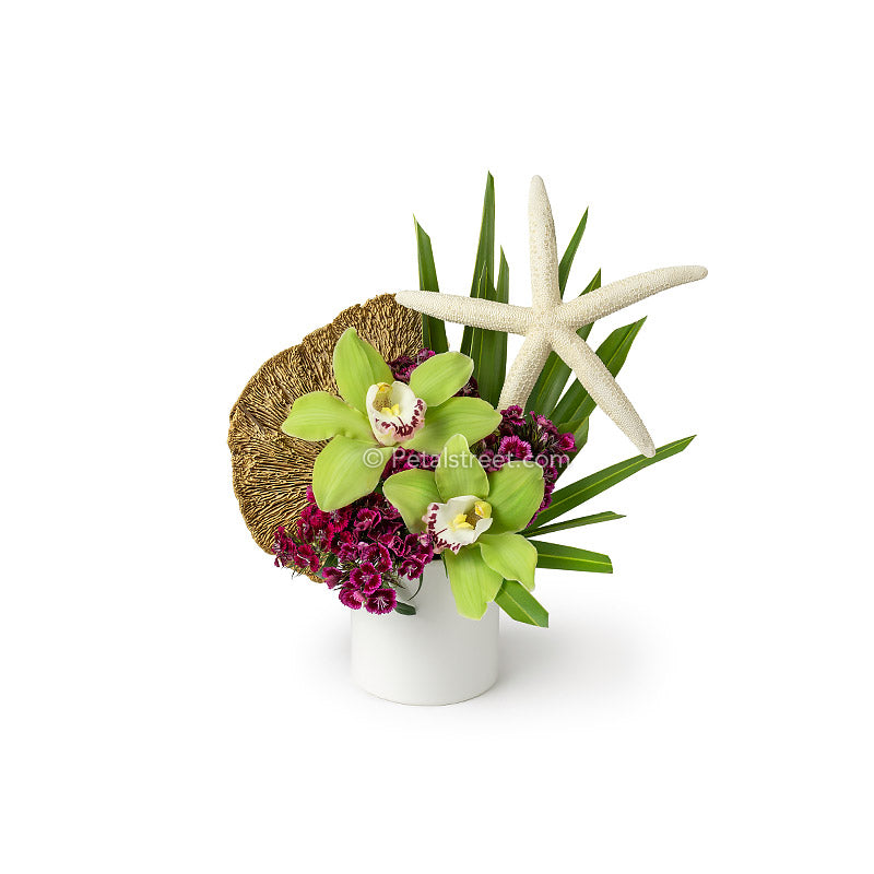 Beach inspired flower arrangement in a white vase with green Orchids, Palm Leaves, magenta Sweet William, and a large starfish