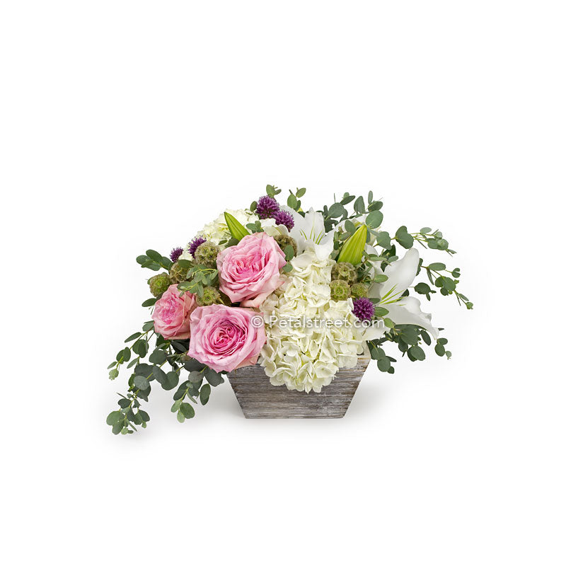 Pink Roses, white Hydrangea, and Eucalyptus arranged in a white washed box.