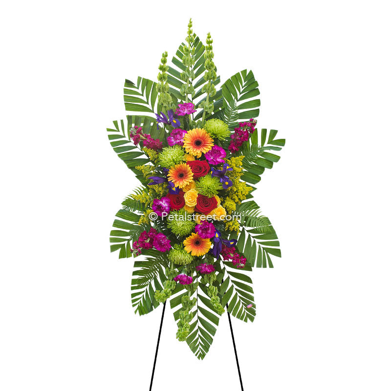 Colorful standing spray with yellow and orange Gerbera Daisies and Roses, floral accents, and lush greenery.