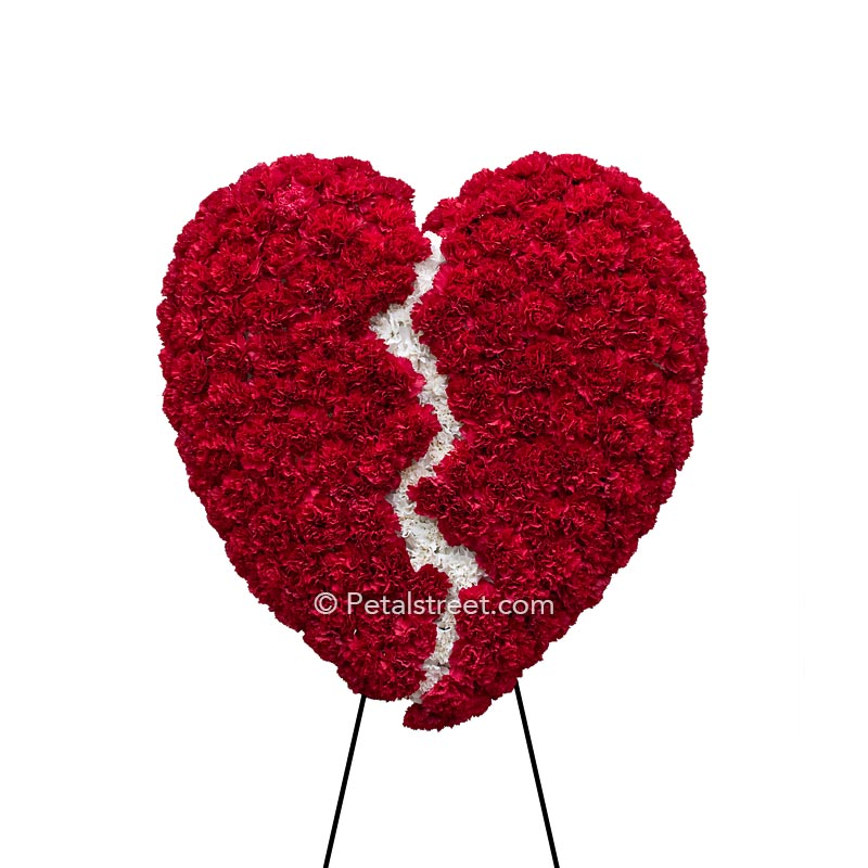 Broken heart form for funeral viewings with red Carnation heart and white Carnation crack down the center.