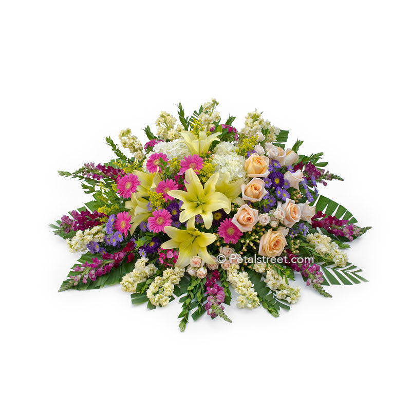 Bright mixed flower casket spray with Lilies, Daisies, Roses, Snapdragons, and accent flowers.