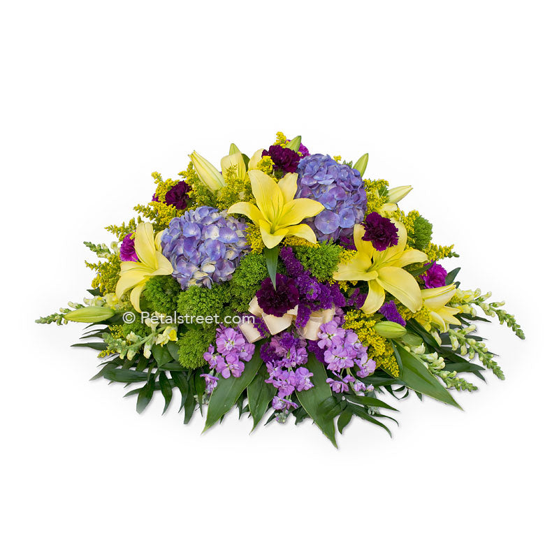 Yellow, purple, and green casket spray with Lilies, Hydrangea, Carnations, and accents flowers.