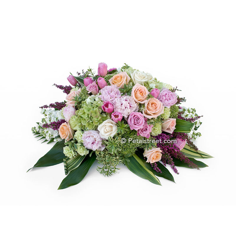 Casket spray with soft pink Peonies, peach Roses, mini green Hydrangea, and Ti Leaf accents.