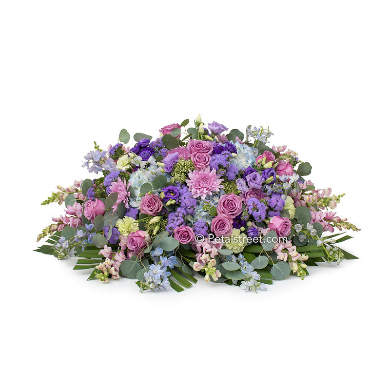 Soft purple, lavender, and blue casket spray with Roses, Hydrangea, and beautiful accent flowers by Petal Street Flower Company.