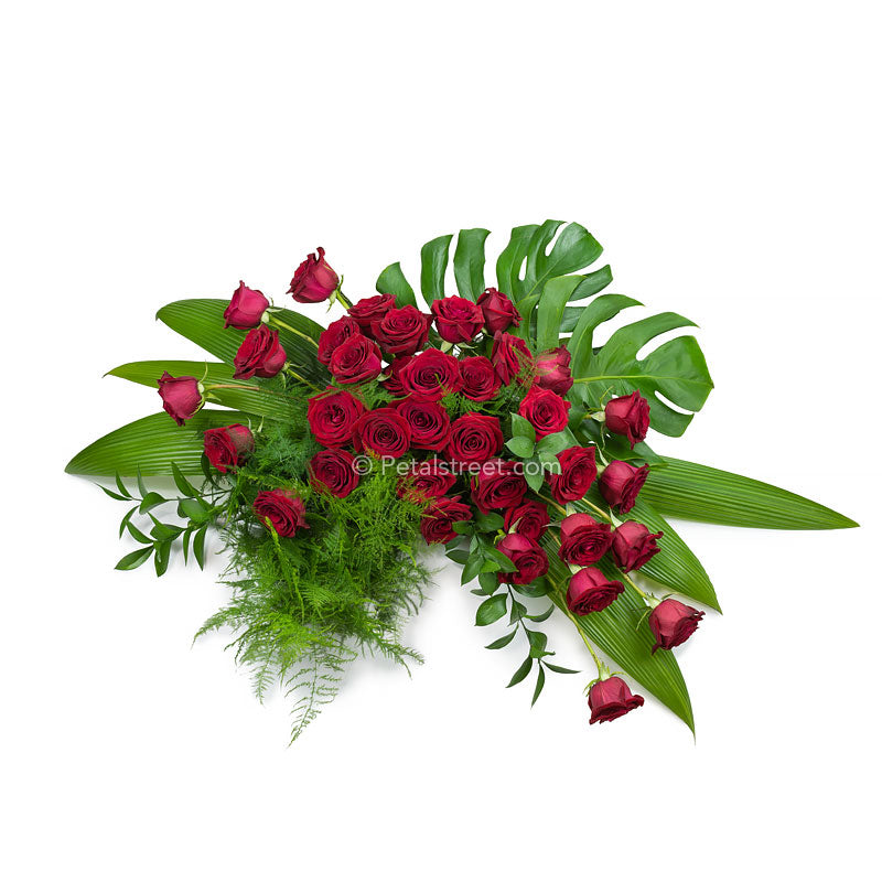 Stylishly designed red Rose Casket Spray with Feather Fern and Ruscus accents, and Accordion Leaves, and Monstera Leaves.