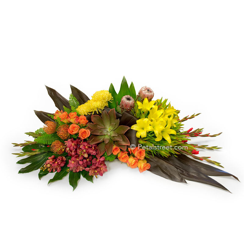 Tropical style casket spray with King Protea, orange Roses, red Orchids, Succulents, and lush green leaves.