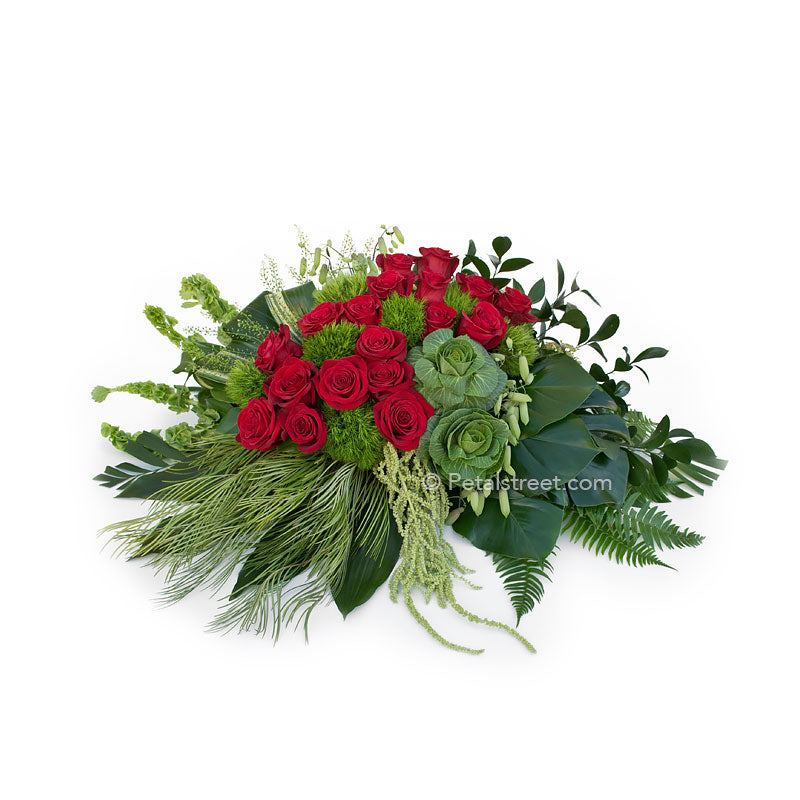 Artisan style casket spray with red Roses, lush Kale, and unique mixed green foliage and textures.
