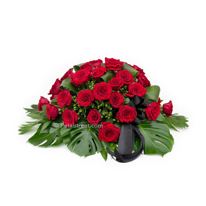 Modern red Rose casket spray with lush tropical leaves.
