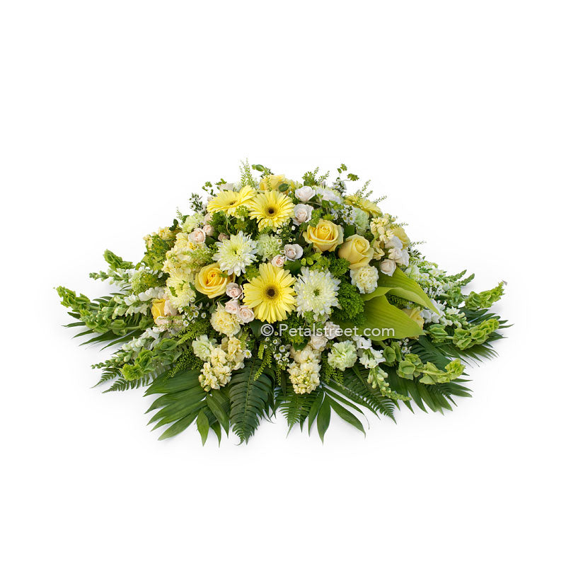 Soft yellow, white, and green casket spray with Daisies, Mums, and Roses by Petal Street Flower Company.