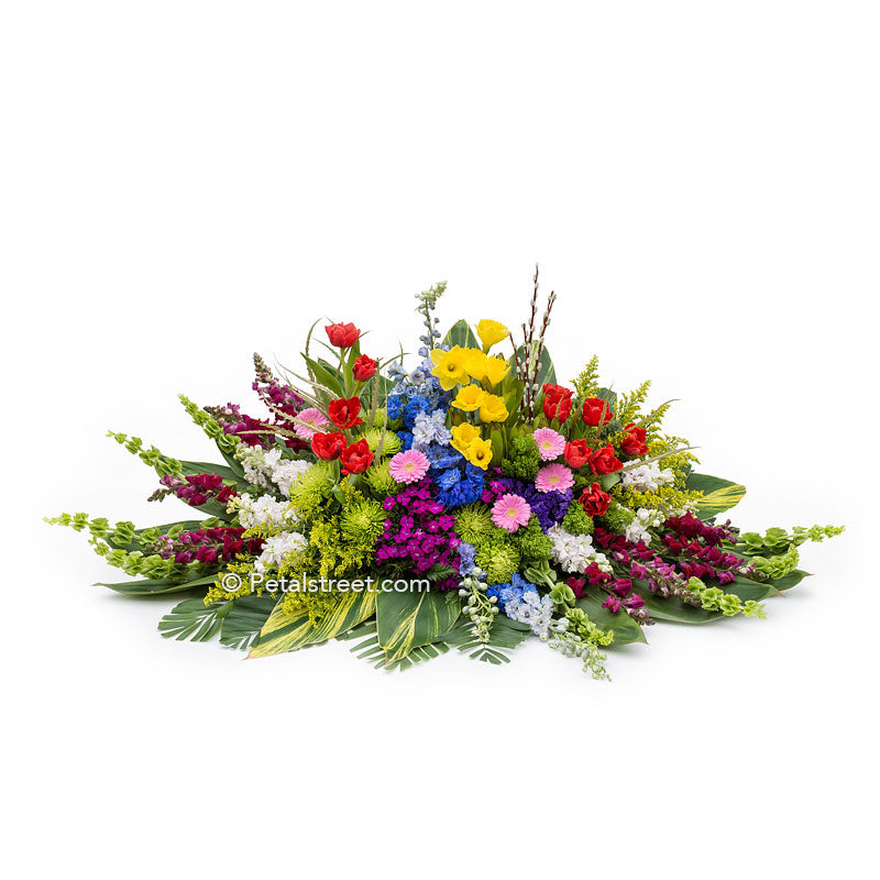 Spring garden casket spray with mixed seasonal flowers such as Tulips, Daffodils, Snapdragons, accent grasses and greenery.