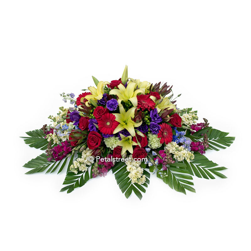 Bright and bold colored casket spray with lilies, Roses, Daisies, Snapdragons, and large leaf accents.