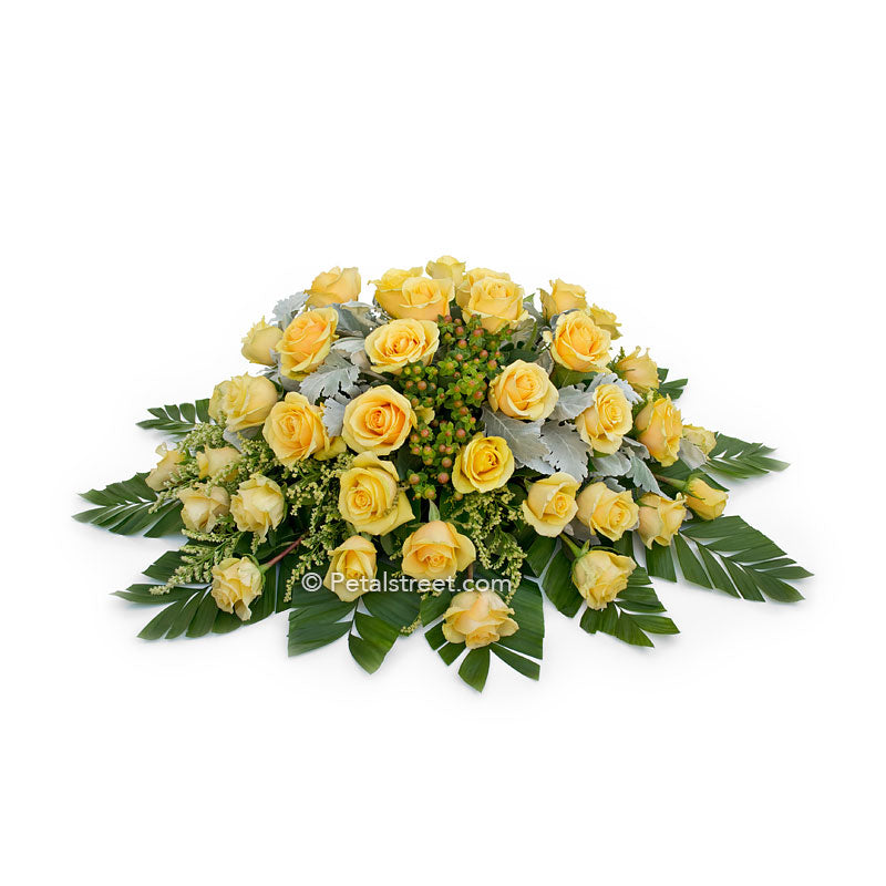 Casket spray with yellow Roses for family funeral viewing.