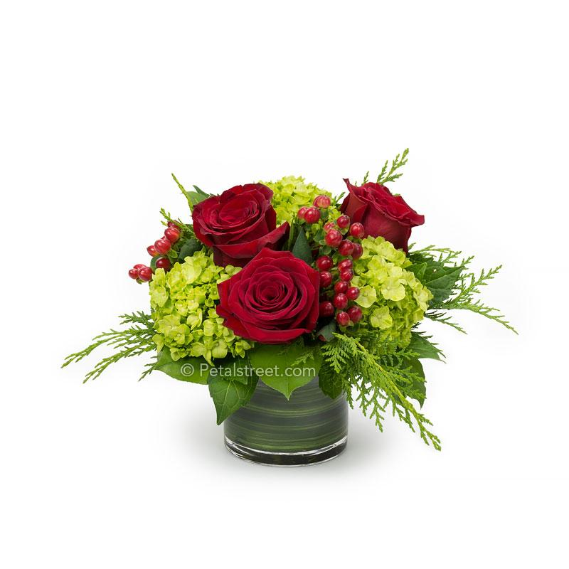a short cylinder vase with red Roses, green mini Hydrangea, red Hypericum Berries, and seasonal greens, Merry Christmas!