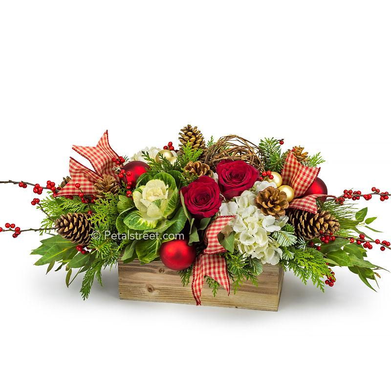 Country Christmas styled flower arrangement with red Roses and Berries, green Kale, white Hydrangea, Pine Cones, red and gold holiday ornaments, plaid ribbon tails, and mixed seasonal greens arranged in a rustic wooden box.