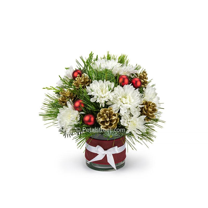 Small Christmas flower vase with white Mums, mixed seasonal greens, gold painted Pine Cones, and red holiday ornament accents.