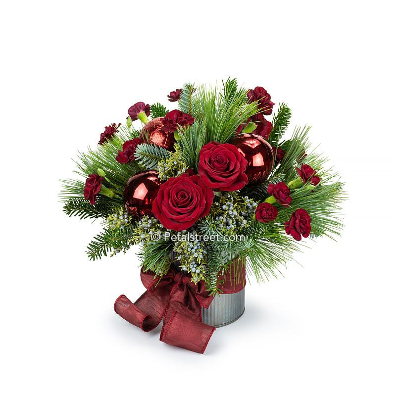 Christmas flower arrangement with red Roses, red mini Carnations, blue Juniper Foliage, mixed seasonal greenery, and large red holiday ornaments in a rustic tin cylinder container with a hand-tied maroon bow.