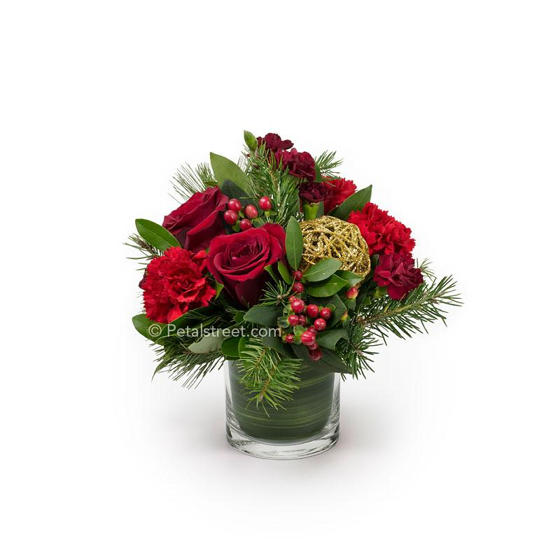 Christmas style flower arrangement with red Roses, Carnations, and Hypericum Berries arranged in seasonal greens.
