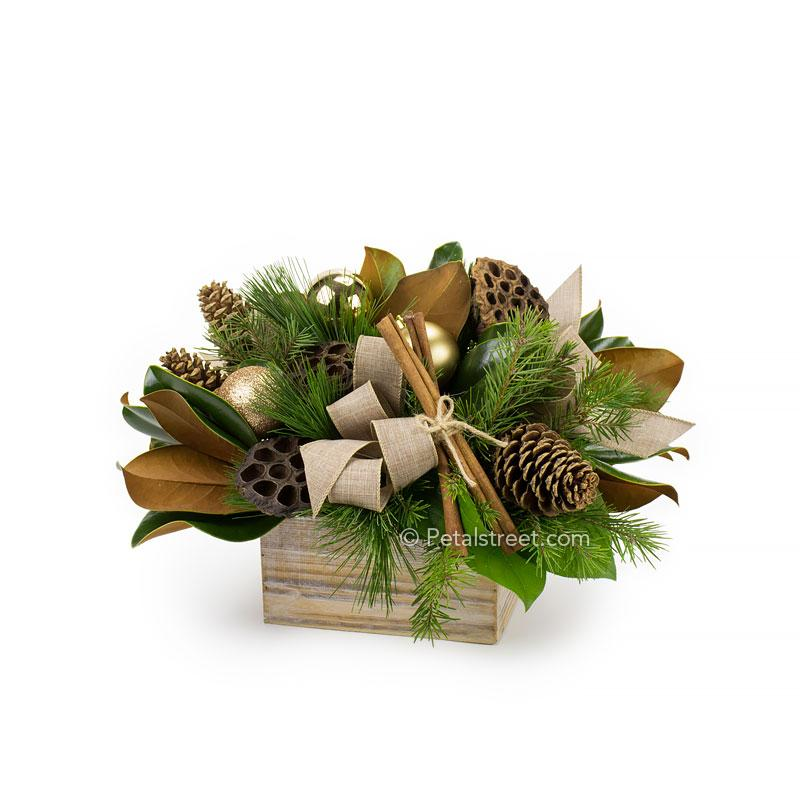 Holiday arrangement in a wood box with Pine and Spruce branches, Magnolia Leaves, Lotus Pods, Pine Cones, Cinnamon Sticks, and gold holiday ornament accents.