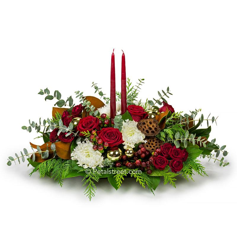 Red, green, and white Christmas table centerpiece with Mums, Roses, Magnolia Leaves, Eucalyptus, mixed seasonal greens, and two red candles.