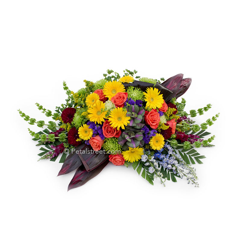 Bright colored casket spray with yellow Daisies, orange Roses, green Spider Mums, and deep earth toned Ti leaves.