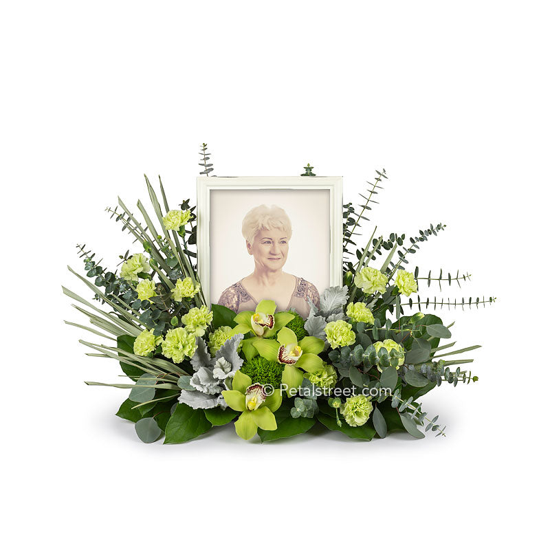 This cremation urn flower arrangement (shown with tribute photo frame) includes Cymbidium Orchids, mini Carnations, Green Trick, Eucalyptus, and accent foliage.