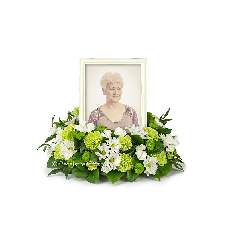 Cremation flower arrangement with tribute photo frame in center includes Daisies, Carnations, Dianthus, Button Mums, and accent foliage.