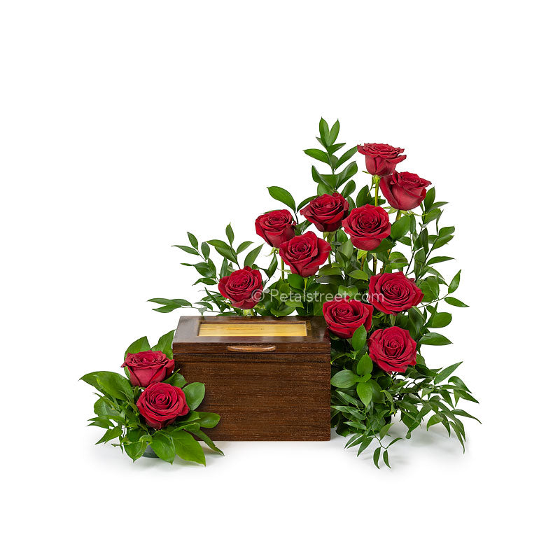 A garden inspired cremation urn flower arrangement with one dozen red Roses and lush accent foliage.