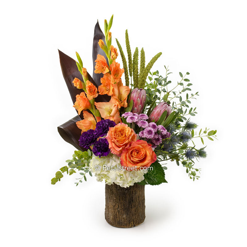 Orange Roses and Gladiolas, plum Carnations and Mums, Protea, Thistle, Hydrangea, and Millet arranged in a Bark cover vase with Ti Leaf accents.