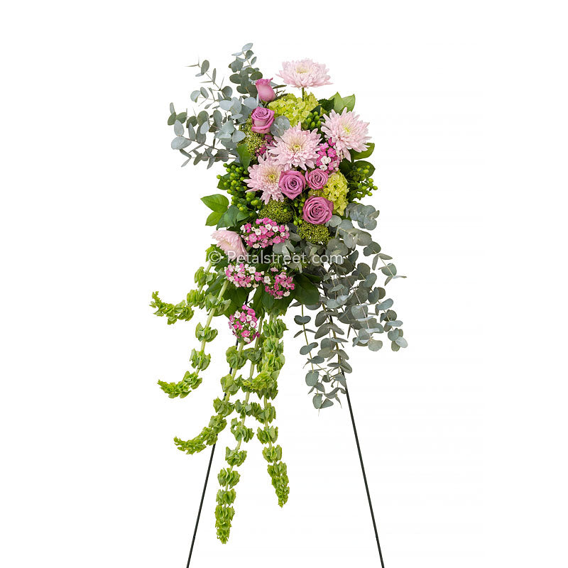 Cascading standing spray with pink Roses, Mums, and Sweet William, green Hydrangea, Eucalyptus, and Bells of Ireland.