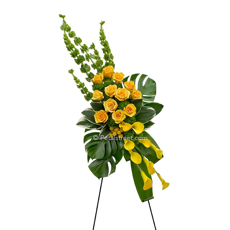 Gorgeous standing spray of funeral flowers, yellow Roses & Calla lilies with large monstera leaves.
