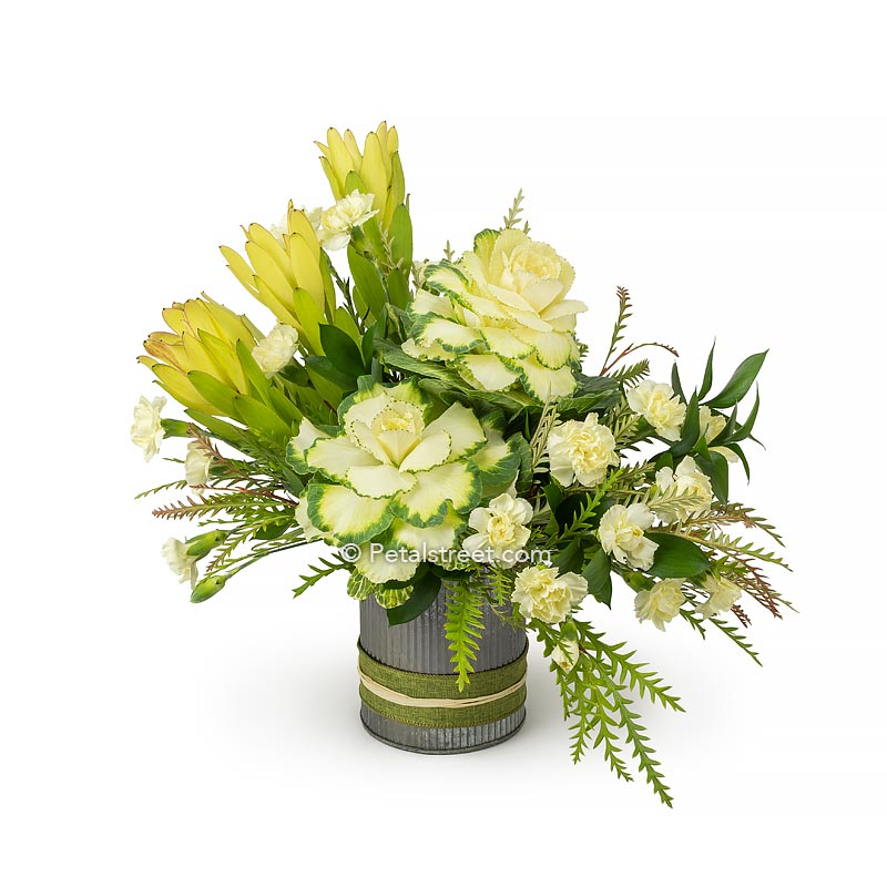 Autumn flower arrangement with cream white kale and Dianthus accent flowers, soft yellow green Leucadendron, and accent greenery in a tin cylinder container