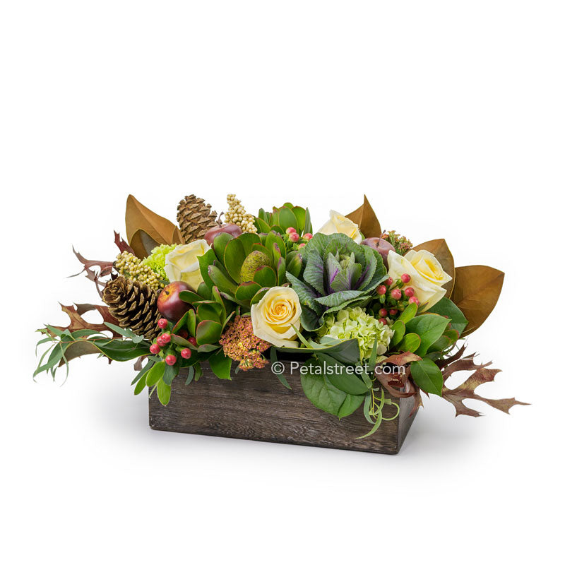 A rustic wood box with a mix of yellow Roses, Kale, Berries, mini Hydrangea, and Pine Cones accented with Magnolia and Oak Leaves.