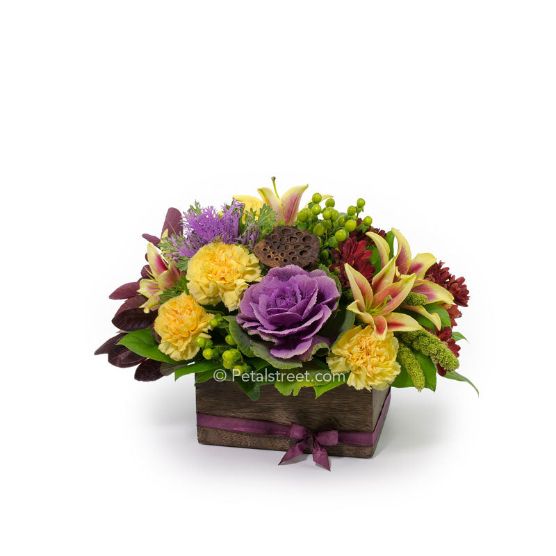 Vibrant mixed Fall flowers such as purple Kale, yellow Lilies and Carnations, red Mums, and green Berry accents in a wood box.