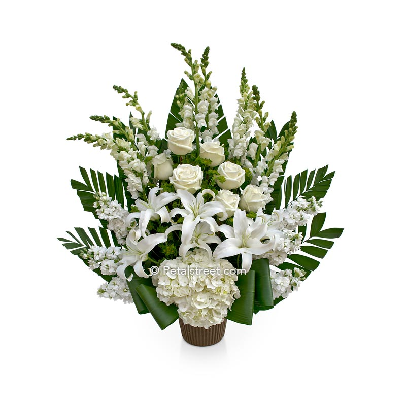 All white flower funeral basket with Lilies, Roses, Snapdragons, and Hydrangea by Petal Street Flower Company florist.