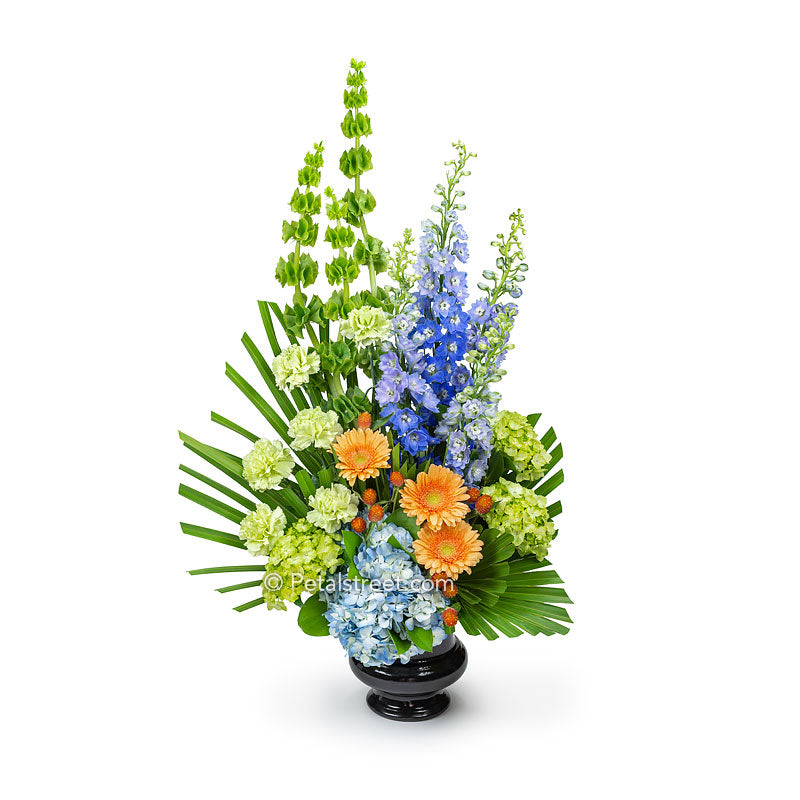 Funeral basket with peach Gerbera Daisies, blue hydrangea and Delphinium, green Carnations, and Bells of Ireland.