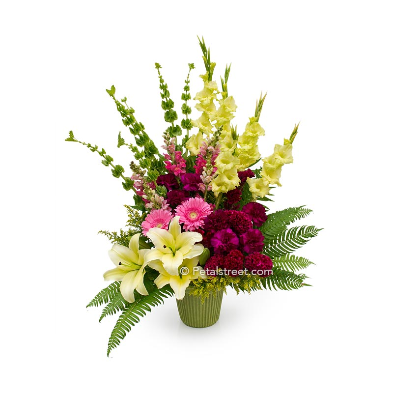 Beautiful funeral basket with pink Daisies, magenta Carnations, Snapdragons, and yellow Lilies and Gladiolas.