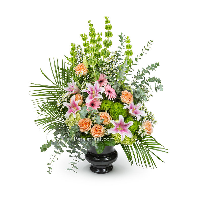 Garden style funeral basket with pink Lilies, peach Roses, green Hydrangea, and a variety of flower and foliage accents.