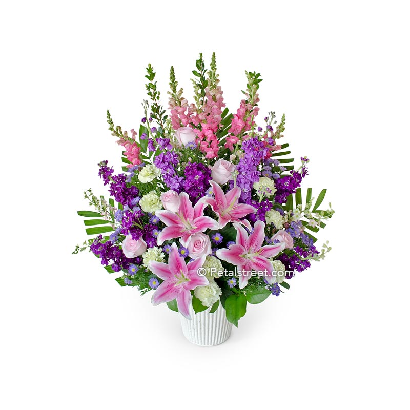 Pink, purple, and white funeral basket with Lilies, Roses, Snapdragons, Stock, Carnations, Hydrangea, and accent greenery.