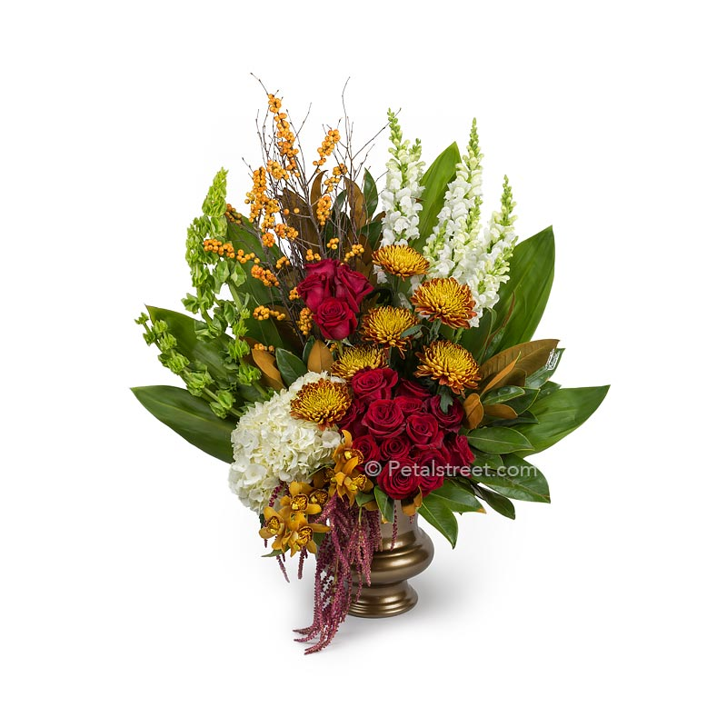 Large funeral basket with red Roses, white Hydrangea and Snapdragons, Mums, Orchids, soft orange Berries, and lush Ti leaves.