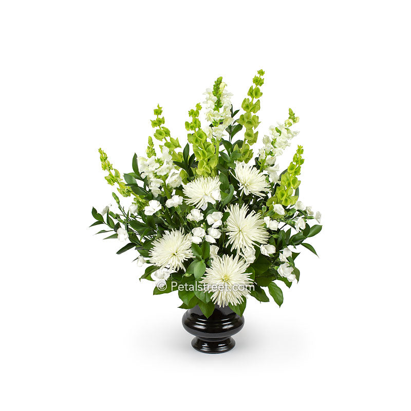Garden style funeral flower basket with large white Mums, mini Carnations, and Snap Dragons, accented with mixed foliage.