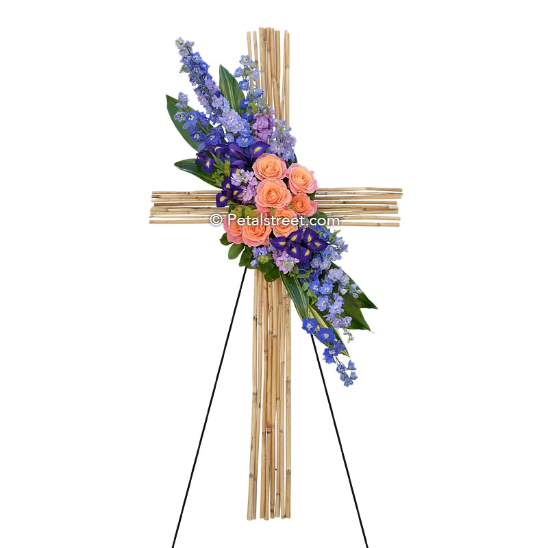 Bamboo funeral cross with orange Roses, purple Aster, and blue Delphinium.
