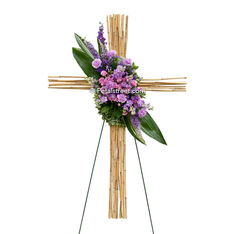 Bamboo funeral cross with purple and pink flowers such as Roses and Carnations.